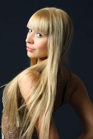 beautiful young woman with luxurious long blond hair against dark background photo
