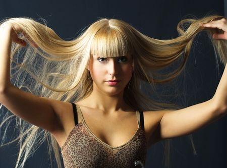 beautiful young  woman with luxurious long blond hair against dark background Stock Photo
