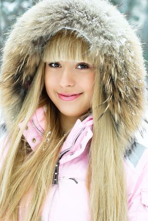 portrait of a beautiful young woman with long blond hair having a walk in winter park photo