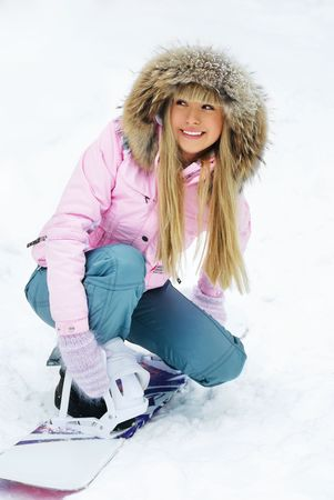portrait of a young beautiful woman on the mountain putting on a snowboard