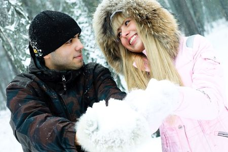 happy young beautiful couple having a walk in winter park and holding snow in their hands photo