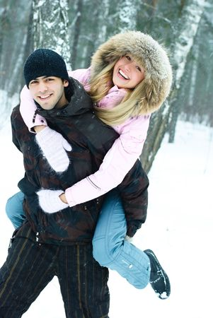 happy beautiful young couple in winter park, young man gives his girlfriend piggyback ride photo