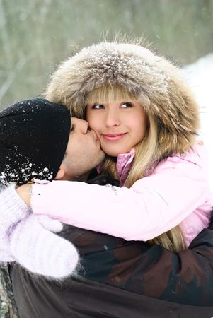 happy beautiful young couple spending time in winter park