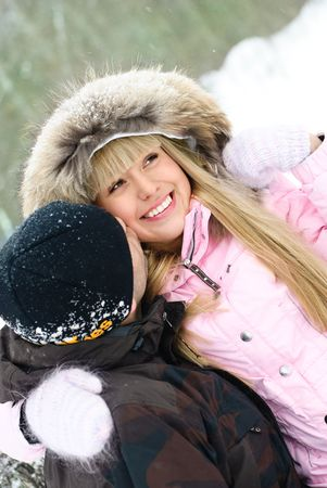happy beautiful young couple spending time in winter park photo
