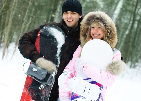 sportswoman: portrait of a happy young beautiful couple with snowboards outdoor
