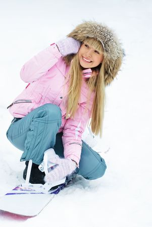 beautiful young woman putting on a snowboard on the mountain photo