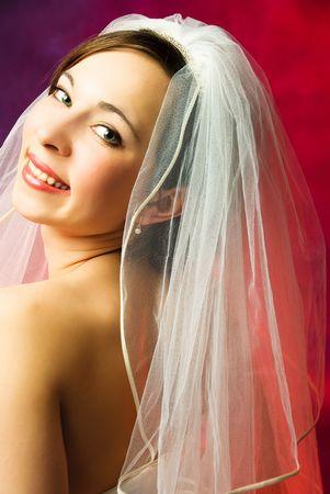 studio portrait of a beautiful young brunette bride wearing a veil photo