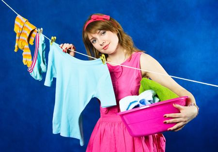 hanging clothes: charming young tired housewife hanging clothes on clothesline using clothespin, against blue background