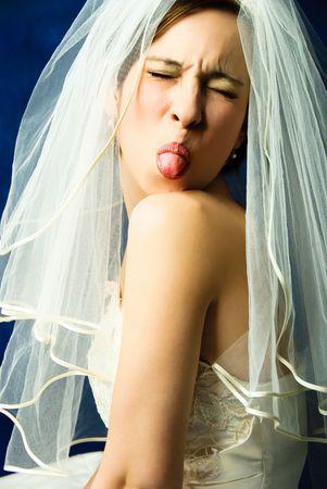 boast: ritratto in studio di una giovane sposa capricciosa mostrando la sua lingua, contro sfondo blu Archivio Fotografico