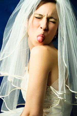 studio portrait of a capricious young bride showing her tongue, against blue background photo