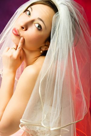 studio portrait of a thoughtful young bride against red background photo