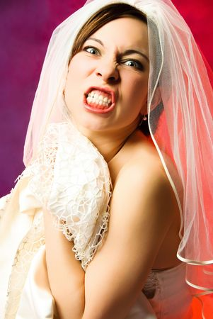 studio portrait of an aggressive young bride against red background photo