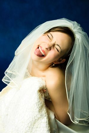 studio portrait of a young bride showing her tongue against red background photo