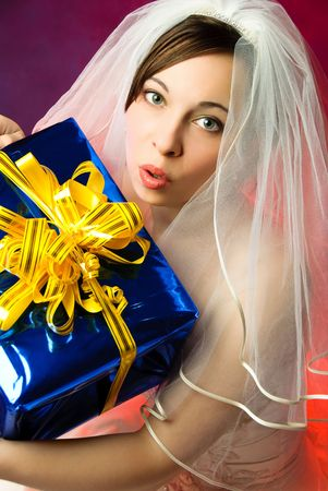 studio portrait of a young surprised bride holding a big present in her hands photo