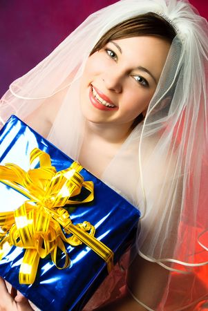 studio portrait of a young bride with a present against red background photo