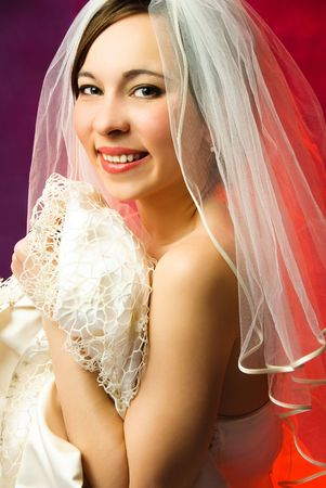 studio portrait of a young brunette bride against red background photo