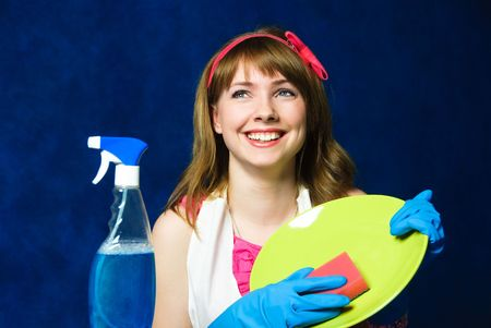 beautiful young housewife washing the dishes against blue background photo