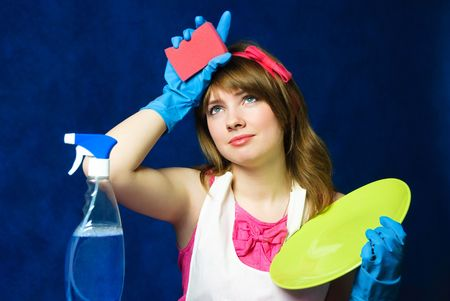beautiful young tired housewife cleaning the dishes against blue background photo