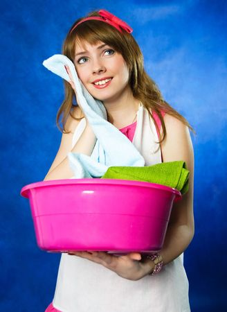 houseclean: beautiful young happy housewife surprised with the softness ot the towels she has just washed