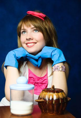 beautiful young housewife sitting by the table with kitchen ware standing on it photo