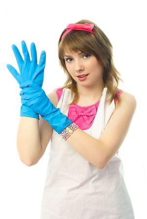 houseclean: beautiful confident young housewife putting on blue rubber gloves