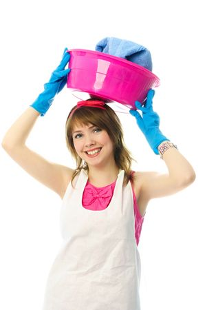 happy beautiful young housewife holding a basin with clean clothes on the head photo
