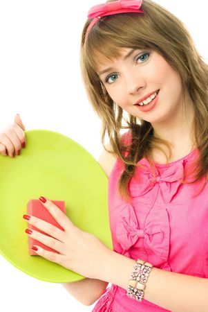 beautiful happy young housewife washing the dishes with a sponge photo