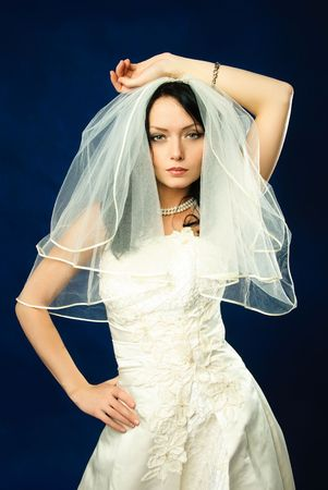 arrogant teen: studio portrait of a beautiful brunette bride against blue background Stock Photo