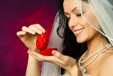 anticiparse: estudio de retrato de una bella morena novia mirando el anillo de boda con una sonrisa Foto de archivo