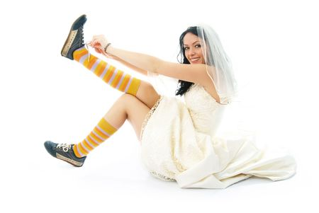 beautiful smiling bride sitting on the floor and putting on old blue trainers  Stock Photo