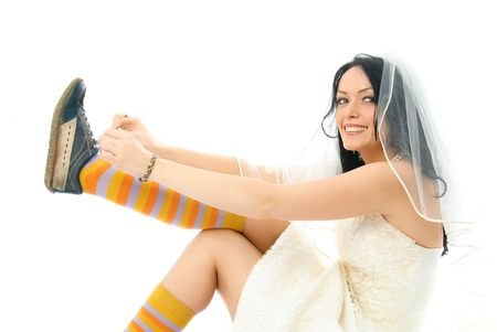 beautiful happy bride sits on the floor and puts on old blue sporting shoes