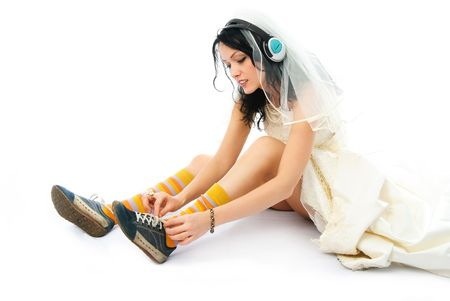 portrait of a modern bride wearing earphones and putting on sporting shoes Stok Fotoğraf