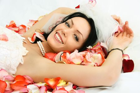 happy beautiful young brunette bride on the bed covered with rose leaves photo