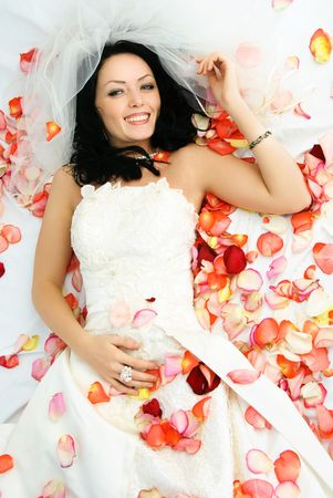 happy beautiful brunette bride on the bed covered with rose leaves photo