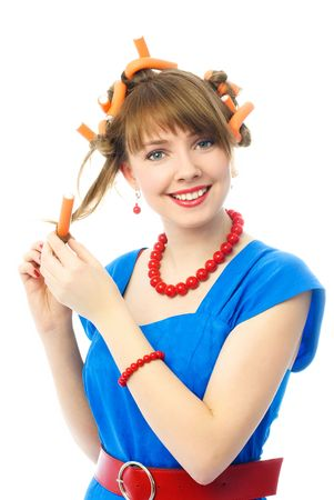 beautiful young woman dressed in retro clothes putting on hair curlers photo