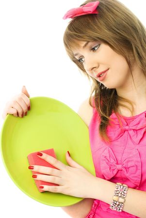 beautiful young housewife washing the dishes with a sponge photo