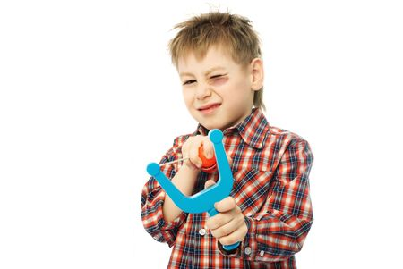 little boy with a bruise and one eye closed aiming at us with a slingshot photo