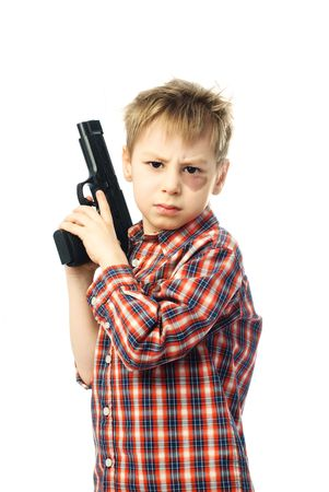 angry boy with a bruise under his eye holding a gun in hands photo