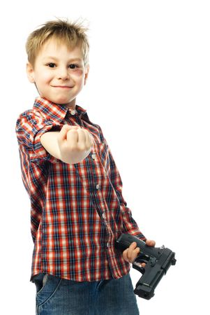 naughty boy with bruise under his eye holds a gun and shows us his fist photo