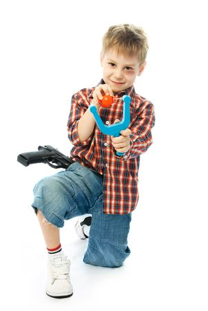 naughty little boy holding a slingshot in his hands and aiming at us Stock Photo