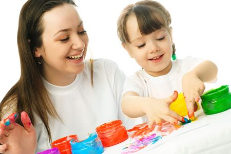 young mother and her daughter painting with finger paints and laughing