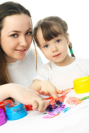 young mother and her daughter sitting by the table and painting with finger paints Stock Photo - 4358402