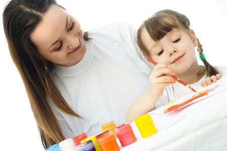 young mother sitting by the table with her daughter and teaching her painting with watercolor Stock Photo - 4358401