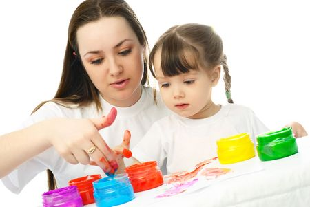 young mother and her daughter sitting by the table and painting with finger paints Stock Photo - 4358393