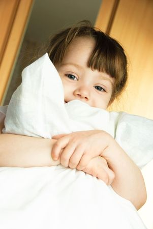 insides: cute little girl embracing a pillow at home in her bedroom