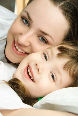 bambini pensierosi: felice ridere sua madre e figlia a letto a casa Archivio Fotografico