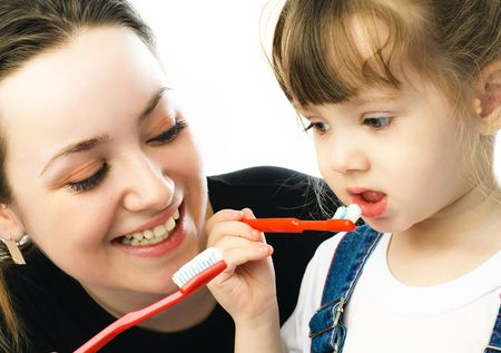 young beautiful mother teaching her daughter brushing teeth Stock Photo
