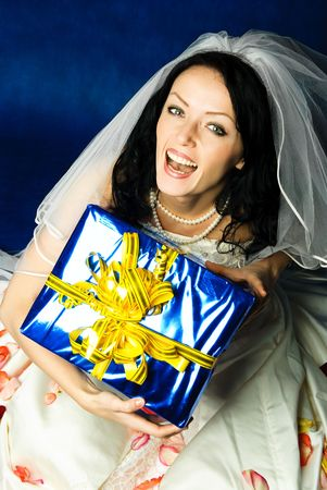 studio portrait of a happy excited bride with a big\ present