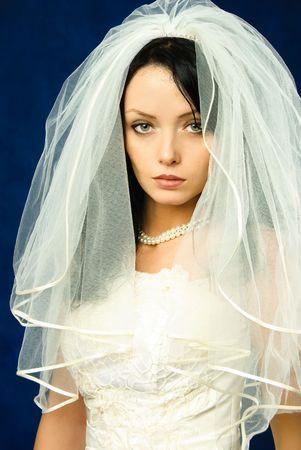 melancholijny: studio portret pięknej melancholijny brunetka oblubienicy przed ciemnym niebieskim tle Zdjęcie Seryjne