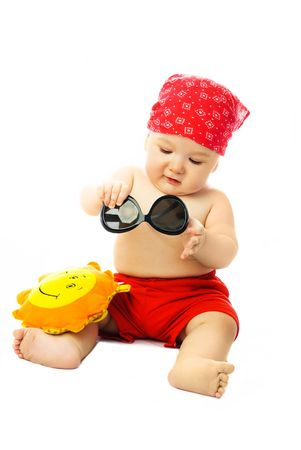 beach wear: cute ten months old baby wearing summer clothes putting on sunglasses